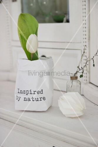 Weisse Tulpe in selbstgefertigter, bedruckter Papiertüte