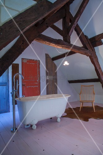 Free-standing bathtub, rustic exposed beams and various vintage doors in converted attic