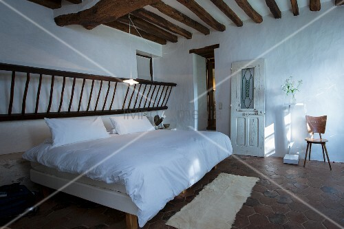 Rustic wooden ladder above head of double bed in bedroom