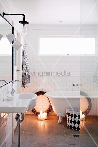 Brennende Kerzen am Boden vor Weidenkranz als Weihnachtsdeko neben Badewanne im Retro Badezimmer