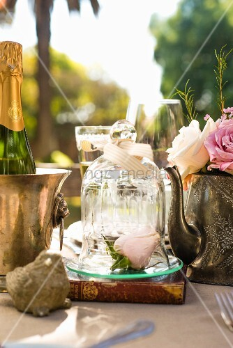 Roses in teapot, rosebuds under glass cover and bottle of Champagne on tea-time buffet