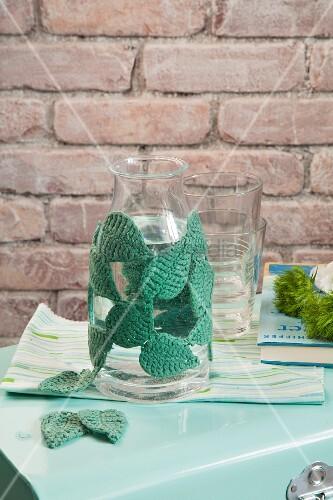 Glasflasche umhäkelt mit Blättermotiven und Gläser vor Backsteinwand