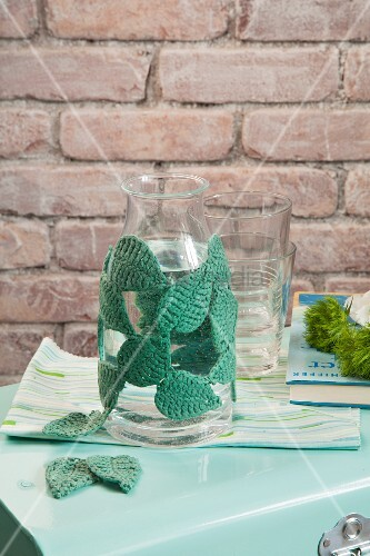Glass bottle with leaf-patterned crocheted cover and drinking glasses in front of brick wall