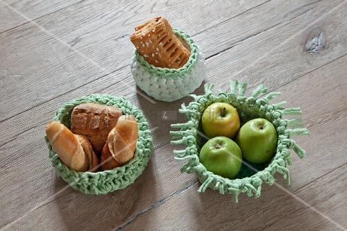 Gehäkelte Körbe mit Äpfeln und Gebäck auf Holzunterlage