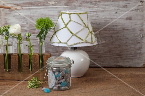 Green chain-stitch net cover on white lampshade next to single flowers in test tube vases