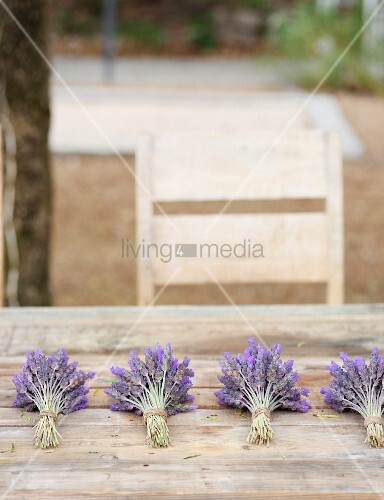 Four lavender posies on wooden table in garden