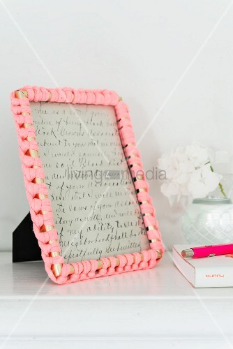 A picture frame with a decorative crochet border made from jersey material