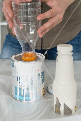 Hanging flower vases being made from plastic bottles