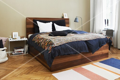 Elegant wooden bed with integrated storage drawer on herringbone parquet floor