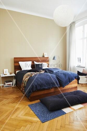 Elegant wooden bed with blue bed linen in bedroom with herringbone parquet floor