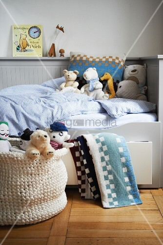 Soft toys on child's bed with pale grey wood cladding and integrated storage drawers