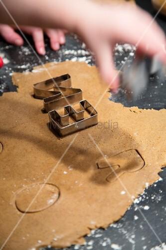 Hände über Plätzchenteig mit Buchstaben-Ausstechern