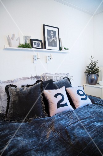 Arrangement of dark velvet bedspread, velvet cushions and scatter cushions with numbers on covers on bed