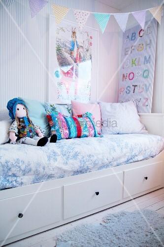 Kinderzimmer in Pastelltönen mit Wimpelkette über dem Bett