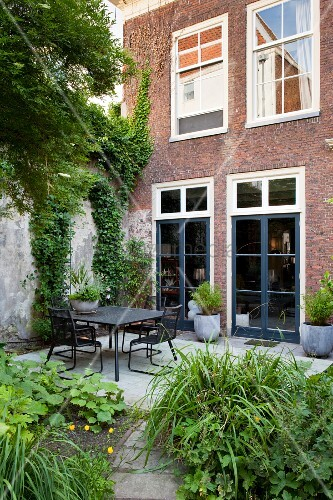 Black outdoor furniture on terrace adjoining renovated brick façade seen from green garden