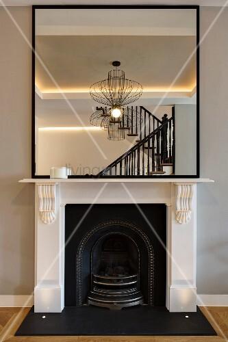 Wandspiegel auf weißem Kaminsims mit gespiegeltem Treppengeländer und Designerlampe in restauriertem Kaminzimmer