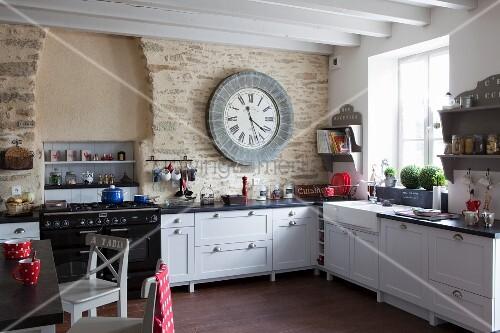 weiße Landhausküche vor Natursteinwand mit großer Wanduhr