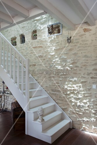 White-painted wooden staircase running up stone wall