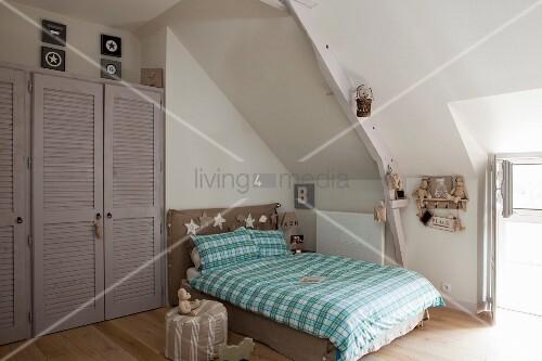 Doppelbett Mit Karierter Bettwäsche Unter Dachschräge, Grauer Einbauschrank  Mit Lamellentüren In Wandnische