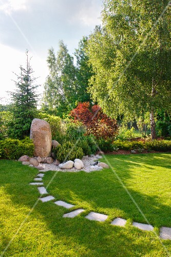 Gardens landscaped with boulders and stepping stones in lawn