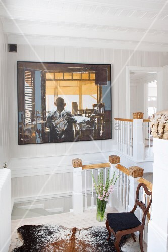 Seating area on landing in open-plan stairwell; antique chair on animal-skin rug and modern artwork on wall