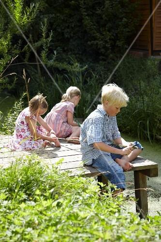 Children playing on wooden jetty next to garden pond