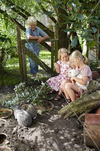 Children feeding rabbits in pen