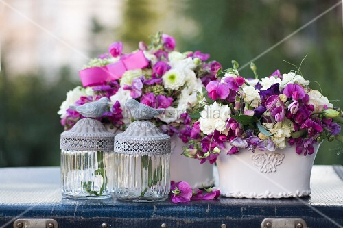 Two romantic flower arrangements and glass candle lanterns with bird figurines on lids on vintage suitcase