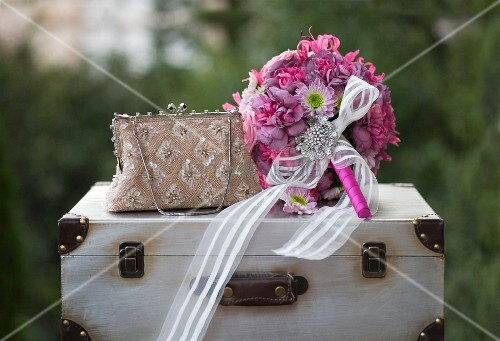 Romantic, pink bridal bouquet with white ribbon and brooch next to elegant handbag on vintage suitcase