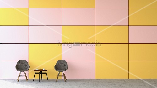 Waiting area with two chairs & coffee table against pink and yellow wall