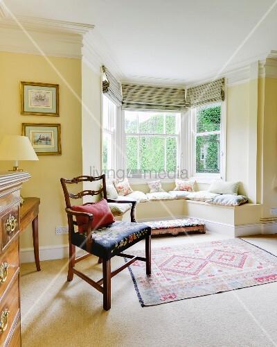 Gelb getöntes Wohnzimmer mit antikem Armlehnstuhl neben Erker mit gemauerter Sitzbank