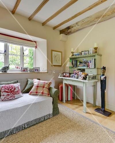 l ndlicher sekret r mit regalaufsatz neben bemalter holzfigur und sofa mit wei em berwurf vor. Black Bedroom Furniture Sets. Home Design Ideas