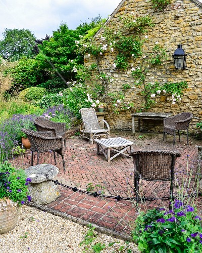Wicker chairs and rustic wooden table in seating area on paved terrace next to flowering rose climbing over stone façade