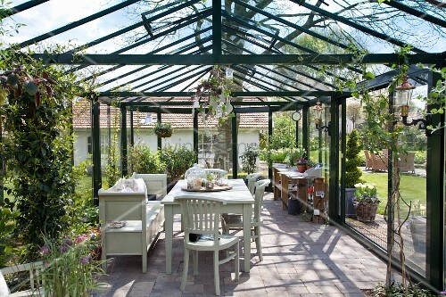 Table and seating in large conservatory in spring garden