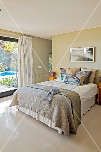 Grey bedspread on double bed next to terrace windows in modern bedroom with pale grey resin floor