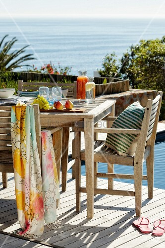 Sunny terrace with wooden table and chairs next to pool with sea view on background