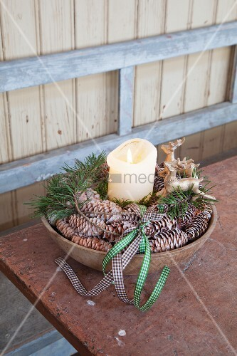 Pillar candle, stag ornaments and pine cones arranged in bowl