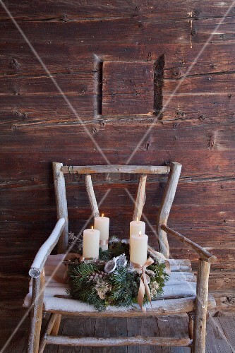 Vintage-style Advent wreath on rustic wooden chair against cabin wall