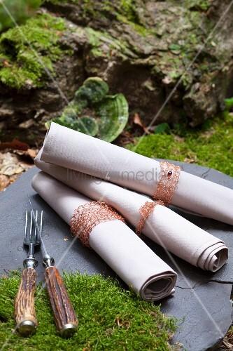Gehäkelte Servietten mit Ringen aus Kupferdraht im Wald