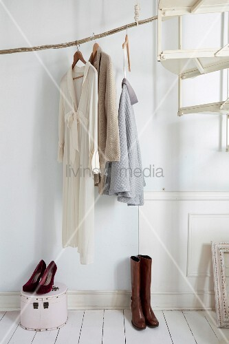 DIY clothes rail made from weathered branch in foyer
