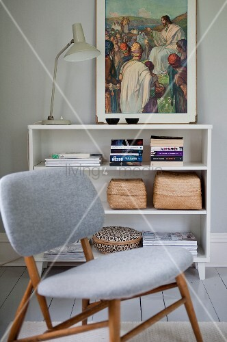 Chair with pale grey upholstery in front of retro table lamp and religious painting on half-height shelving unit