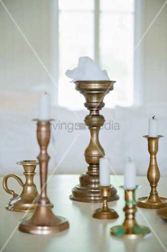 White candles in brass candlesticks