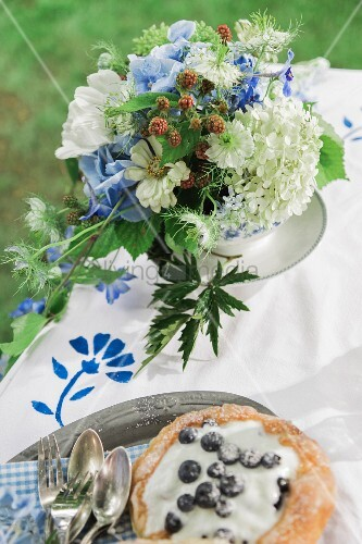 Bouquet of blue and white garden flowers and blueberry tartlet