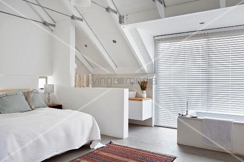 Schlafzimmer Im Weißen Dachgeschoss Mit Offenem Bad, Freistehende Badewanne  Vor Fenstern Und Geschlossener Jalousie