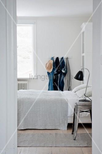 Weißes Schlafzimmer mit Jeanshosen an einer Hakenleiste