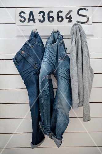 Jeans and jumper hanging from coat pegs on board wall