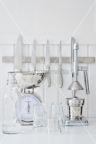 Kitchen knifes on magnetic strip, scales, juice squeezer and glasses