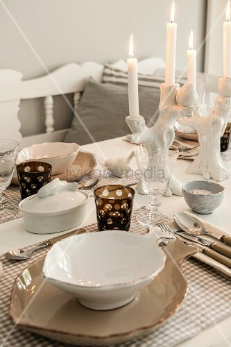 Place setting with elegant, leaf-shaped china bowl and lit candle in china candlestick on dining table