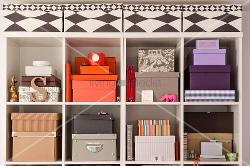 Colourful storage boxes stacked on open-fronted white shelves