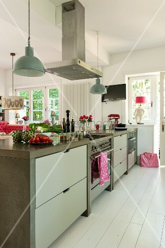 Free-standing kitchen counter with integrated gas cooker under extractor hood in country-house-style kitchen